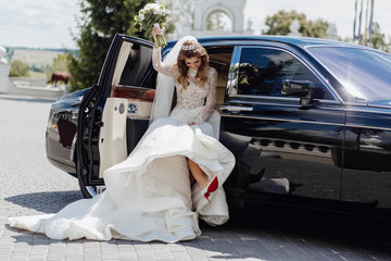 Elegant Bride with Roses Bouquet near Limousine. Sharming Cute Young Woman Dressed in Wedding Garments and Diamond Diadem. Girl Sitting in Black Marriage Car Lift Up Hand with Flower Bunch and Leg