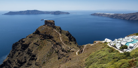 Beautiful view of the Skaros Rock and Nea Kameni on the blue water background on Santorini, Greece.