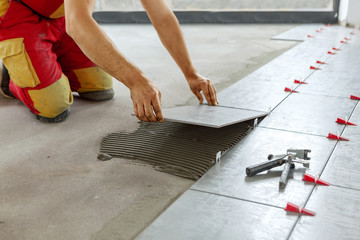 Ceramic Tiles. Tiler placing ceramic wall tile in position over adhesive with lash tile leveling system - Image Fototapete