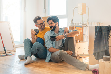 Cute gay couple sitting on floor and enjoying coffee in new home  - Stock image