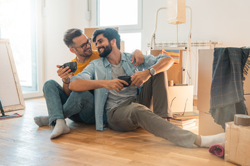 Smiling gay couple sitting on floor and enjoying coffee in new home  - Stock image