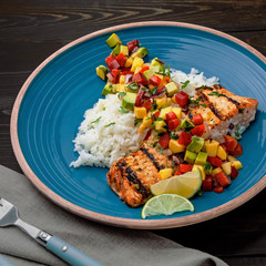Salmon fillet cooked on grill with exotic sauce made of mango, avocado and pepper on blue plate. Delicious fish meal with jasmine rice on a table.