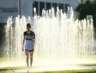 A young woman walks through a water fountain in the government quarter in Berlin