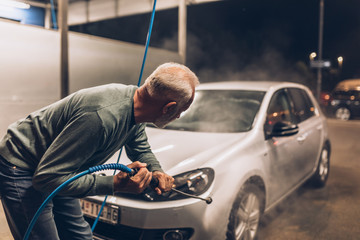 Senior man washing his car in the evening at car wash station using high pressure water.