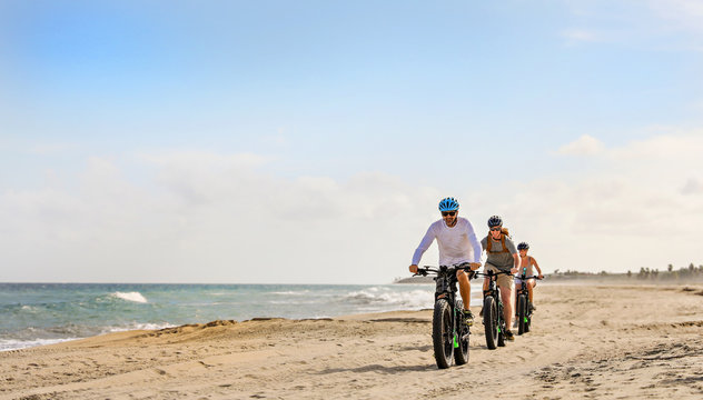 Family rides their e bikes on the beach in the Baja.