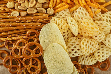 Salty snacks. Pretzels, potato chips, crackers on brown paper. Unhealthy products.