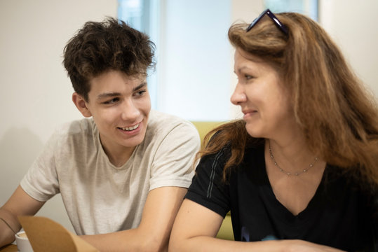 The teenager communicates with his mom in the cafe and smiles. Mom looks at her son with love and does not believe that he grew so fast. Focus on the guy