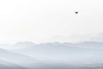Flying drone from the distance in the mountains area with white background