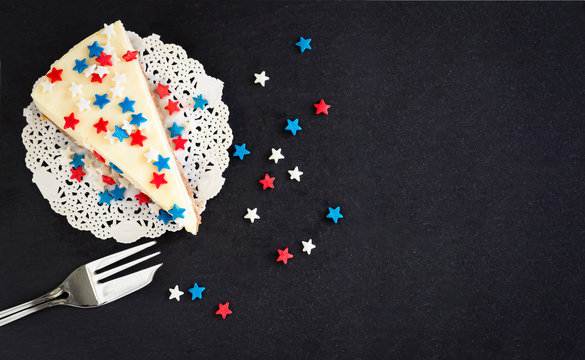 Slice plain new york cheesecake on slate board. Concept celebration of Veteran's Day or July 4th USA. Selective focus. Copy space. Top view flat lay