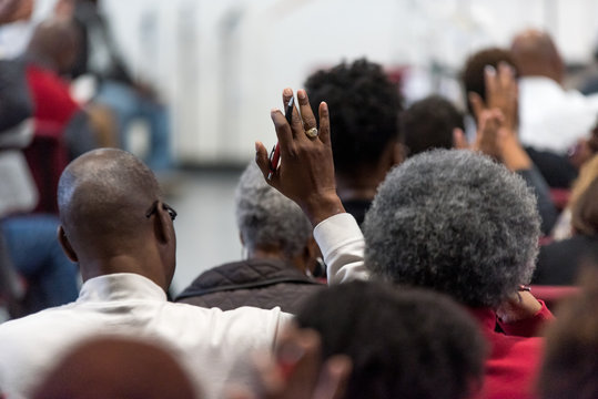 African American Man in a White Suit at Church with His Hand Raised