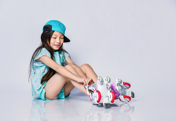 Smiling little asian baby girl in cool hat cap sits on the floor and puts on roller skates on white