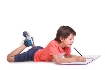School boy lying on floor and drawing with pencil, isolated on a white background