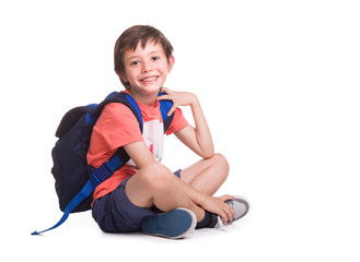 Happy smiling school boy siitting on the floor, isolated on a white background