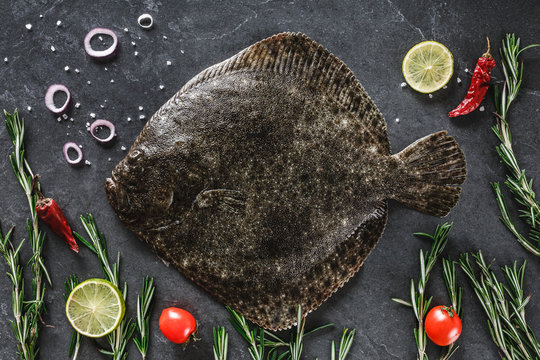 Raw whole flounder fish with rosemary, onions and spices on dark stone background. Creative layout made of fish, top view