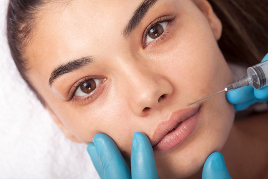 Young woman undergoing procedure of bb glow treatment in beauty salon