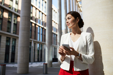 Waist up portrait of elegant young woman looking away pensively while posing outdoors in city, copy space