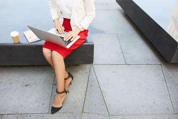 High angle close up of unrecognizable businesswoman typing on laptop keyboard while working outdoors, copy space