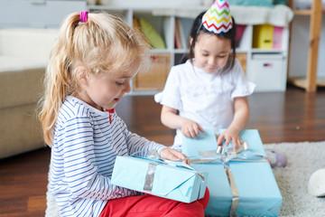 Fotobehang Apotheek Cute blonde little girl unpacking her birthday gift