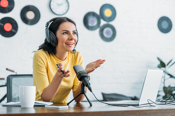 smiling radio host gesturing while recording podcast in broadcasting studio