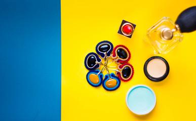 Modny kolaż zawierający ręcznie szyte kolczyki sutasz, szminkę, perfumy oraz kolorowe kosmetyki w ujęciu top view na żółto niebieskim tle