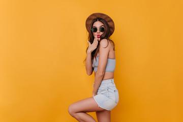 Refined shapely girl wears blue denim shorts playfully posing in studio. Indoor portrait of graceful dark-haired female model in hat and sunglasses. Fotoväggar
