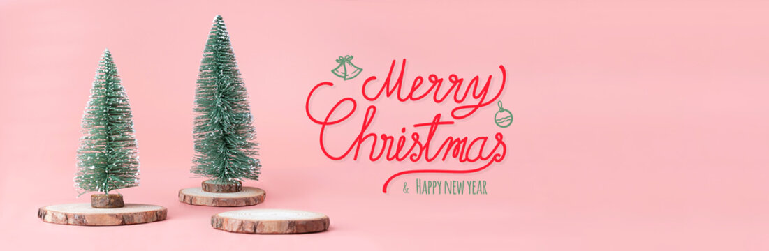Merry Christmas and happy new year word at christmas tree on wood log slice with present box on pastel pink studio background.Holiday festive celebration greeting card.copy space for add text.