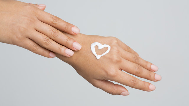 Love your Body. Female Hand with Cream in Heart Form