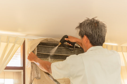 Worker cleaning wall air conditioner with high pressure water jet pump at home.