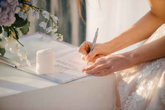 the bride in a wedding dress signs in the contract