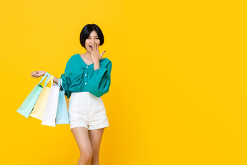 Young cheerful shopaholic Asian girl with shopping bags Wall mural