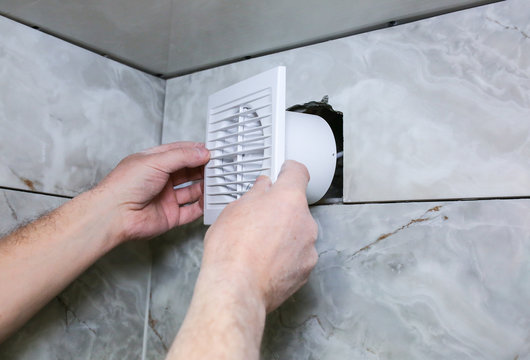 Man is installing the wall bathroom fan vent. Restoration process.