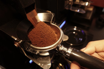 freshly ground coffee beans in a porta filter by the coffee grinder roasted make beans into a powder.