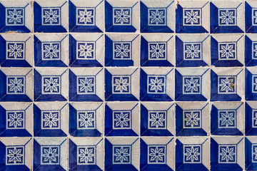 a fragment of the outer wall of a house in Lisbon decorated with ceramic tiles with a beautiful geometric pattern.