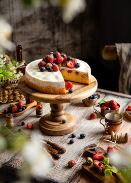 Homemade raspberry sliced biscuit cake with white cream and berries on top on wooden cake stand