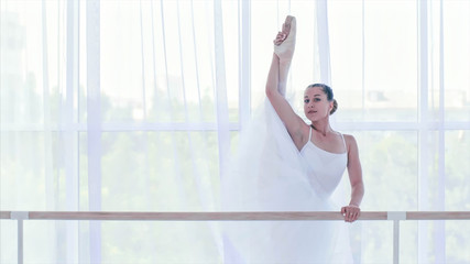 Professional ballet dancer is stretching her legs on the