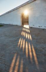 The sun rays break through the grating doors of the wall of Tobolsk Kremlin. Tobolsk. Russia