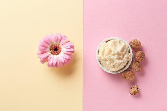 Shea butter with nuts and flower on color background