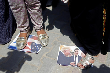 Palestinian woman steps on a picture of U.S. President Trump, Israeli PM Netanyahu and White House senior adviser Kushner during a protest in Gaza City