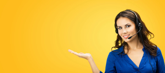 Call center service. Customer support phone sales operator in headset showing something or copy space area for some text, over yellow orange color background