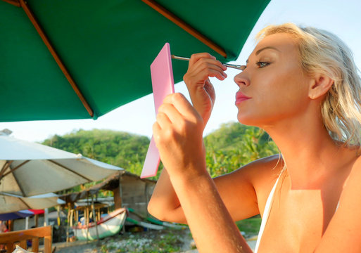 young beautiful and relaxed blond woman holding mirror retouching makeup applying brush eye shadow sitting at holidays beach resort in fashion and beauty concept