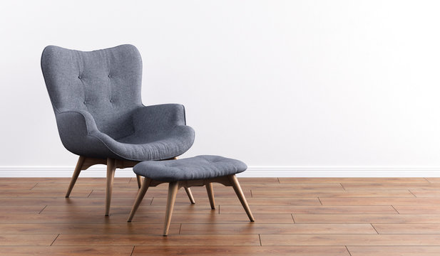 Fashionable modern gray armchair with wooden legs, ottoman against a white wall in the interior. Furniture, interior object, modern designer armchair. Stylish minimalist interior