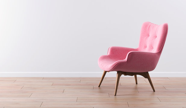 Fashionable modern pink armchair with wooden legs against a white wall in the interior. Furniture, interior object, modern designer armchair. Stylish minimalist interior