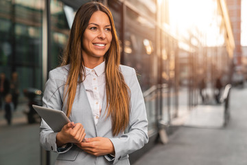 Beautiful business woman using digital tablet outdoors - Stock image