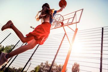 Dark-haired tall teenage girl with basketball skills throwing ball