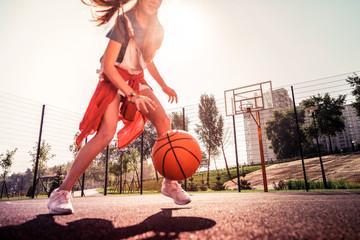 Experienced dark-haired young girl running around basketball playground