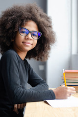 Dark-skinned girl sitting at the table teaches lessons.