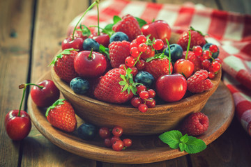 Fresh mixed berry fruits in wooden bowl