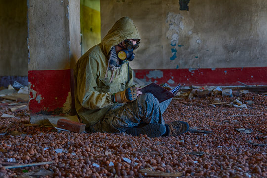 Man in respirator gas mask, steampunk glasses, hood and camo pants sits on the floor inside of abandoned building and reading book. Cyberpunk postapocalypse fantasy horror scene, or air pollution