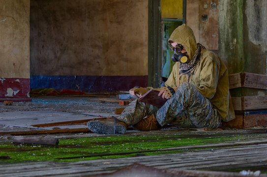 Man in respirator gas mask, cyberpunk goggles, hood and camo pants sits on the floor inside of abandoned building and reading book. Cyberpunk postapocalypse fantasy horror scene, or air pollution
