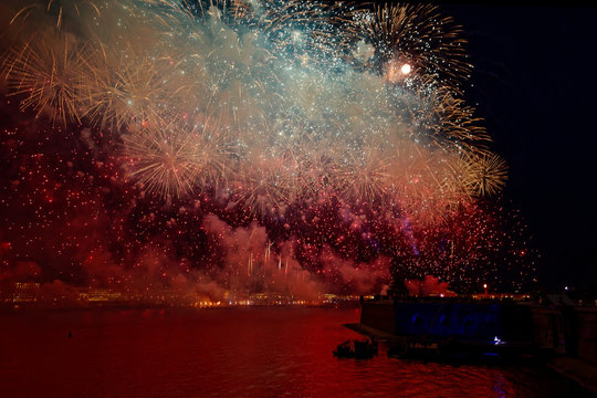 Fireworks over the water Holiday light. Night cityscape scene. Neva river, Saint-Petersburg, Russia. Holiday Scarlet Sails.